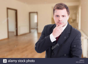 Portrait of young realtor inside of empty flat thinking on selling hgrcp1